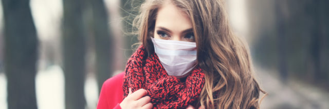 Woman wearing face mask and winter coat.