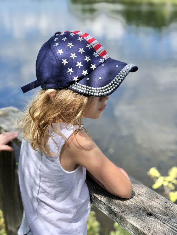 a young girl wearing an american flag cap looking into the distance
