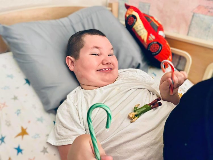 Lori's son lying in bed eating a candy cane.