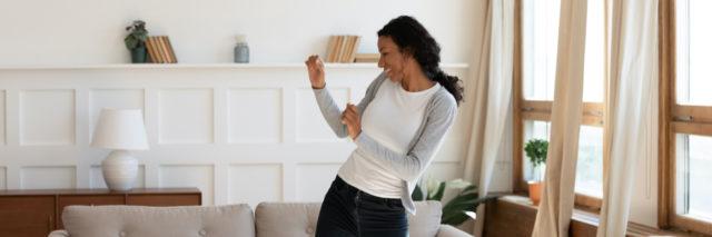 Joyful woman of color dancing in living room