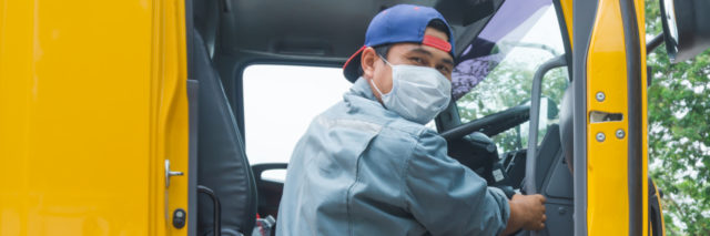 A driver wearing a mask stepping into his truck