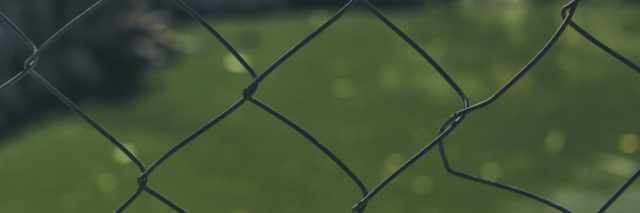 a steel fence with a field in the background
