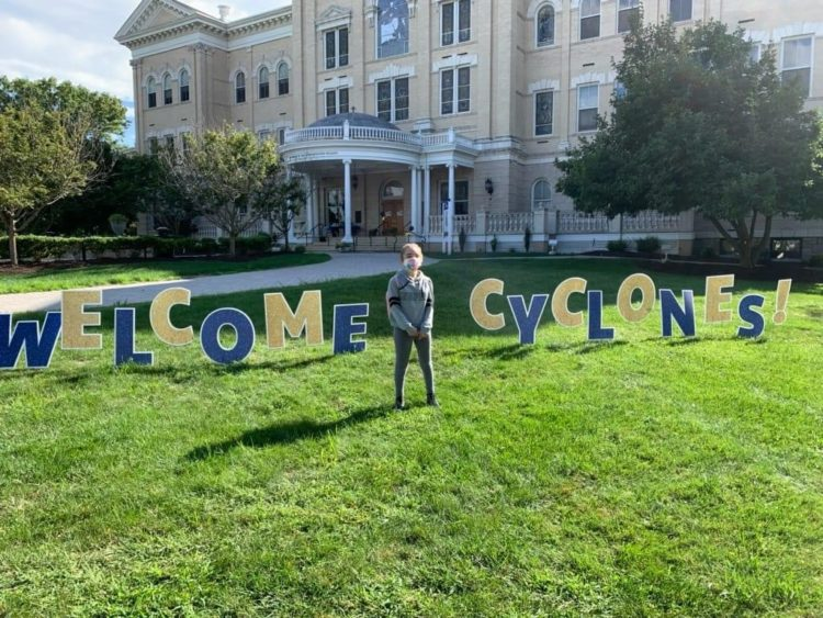 "Standing outside on the grass in front of a school with a blue and gold sign that says ""Welcome Cyclones."""