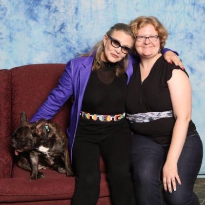 Photo of author sitting on a red couch with Carrie Fisher