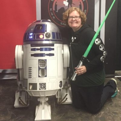 "Photo of author kneeling next to a ""Star Wars"" figure with a green lightsaber"