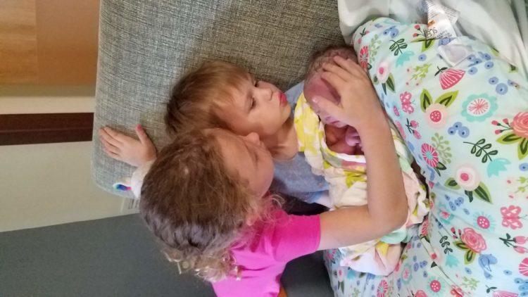 Lindsay's kids cuddling their baby sister.