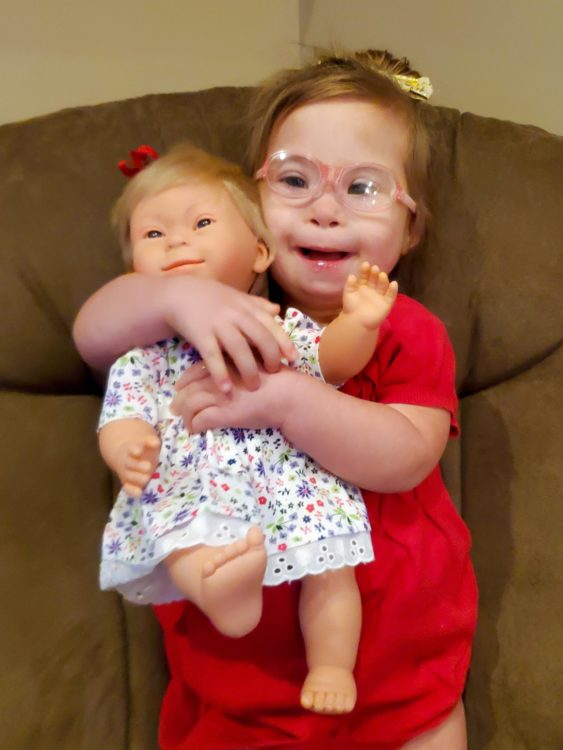 Ivy with her doll that has Down syndrome.