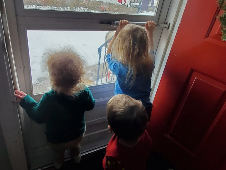 three young children looking out a window