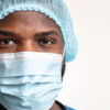 Close up of a Black health care working wearing a cap and surgical face mask