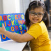 girl with Down syndrome playing with alphabet puzzle toy.