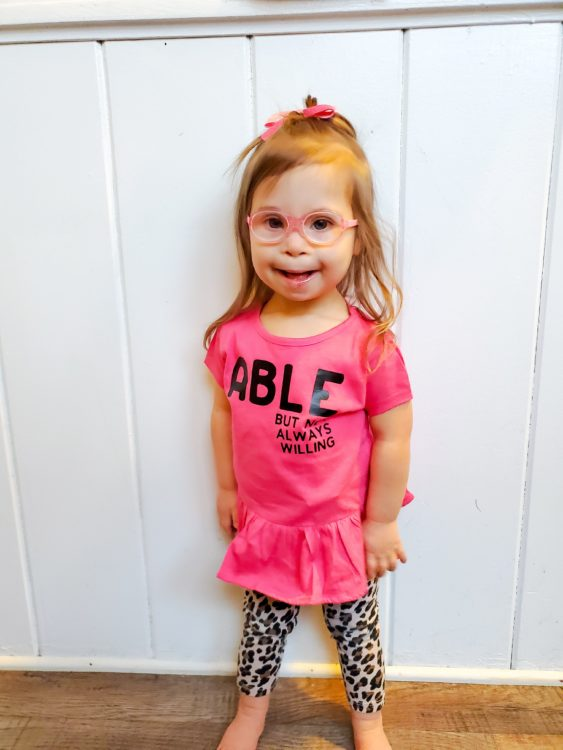 Ivy wearing a pink shirt that says Able.