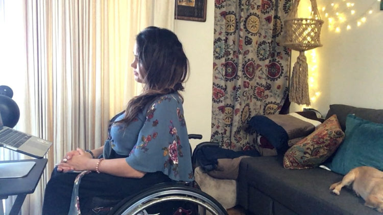 Actress Santina Muha, a woman with long brown hair wearing a blue floral print shirt and sitting in her wheelchair facing a computer screen