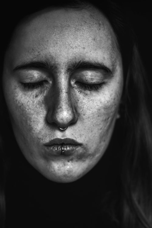 black and white photo of a white woman's face with eyes closed, lips pursed