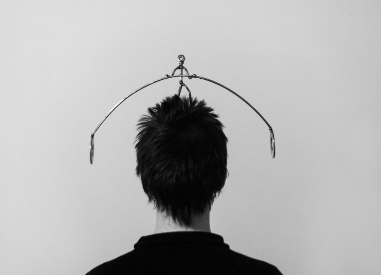 black and white photo of the back of someone with short, spunky hair and a metal rod over the head