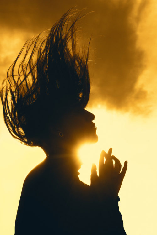 photo of author; young white woman with hair flying above her head as the sun shines on her face