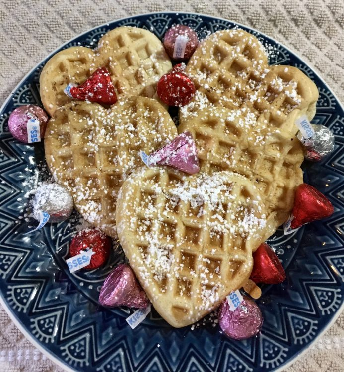 Clear image of waffles with powdered sugar and chocolate.
