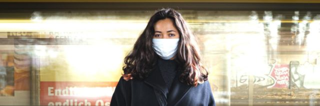 photo of a woman wearing a face mask, standing looking into a camera with a train moving past behind her