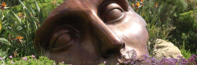 A broken ceramic mask sitting in a field, close up.