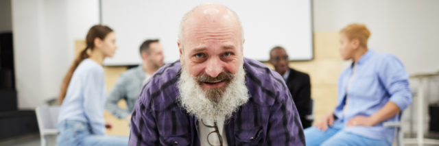A bearded elderly white man in a flannel shirt sitting in a chair smiling with a support group behind him in a circle