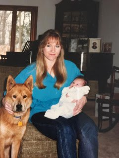 Photo of contributor as a baby being held by her mother, next to a dog