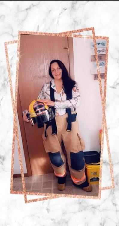 A woman holding a firefighter's helmet