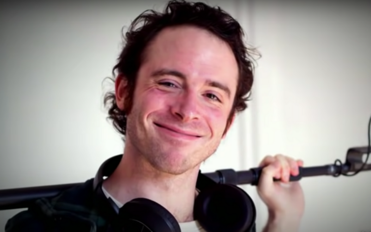 screenshot of sound mixer Michael Wolfe Snyder, smiling for the camera with a mic stand over his shoulders