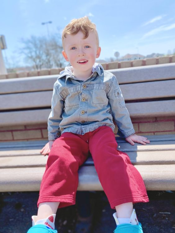 Jacquelyn's son sitting on a park bench..