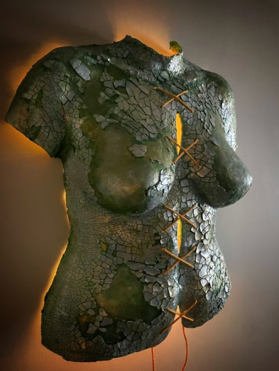 """Body cast sculpture """"Broken Body"""": torso in sea green color, covered in shining, cracked silvery pieces. String tied down the middle in a series making an """"X"""" shape lit from behind"""