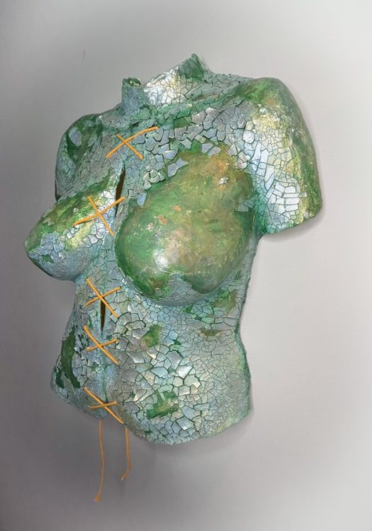 """Body cast sculpture """"Broken Body"""": torso in sea green color, covered in shining, cracked silvery pieces. String tied down the middle in a series making an """"X"""" shape (shown from right angle)"""
