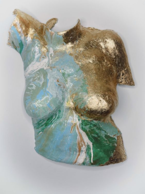 """Body cast sculpture """"Enduring Spirit"""" of torso with one side painted in gold and the other in a mix of swirling green, white and blue (shown from center angle)"""