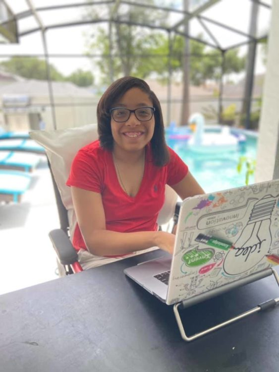 Author, a young Black woman sitting by the pool with her laptop open smiling