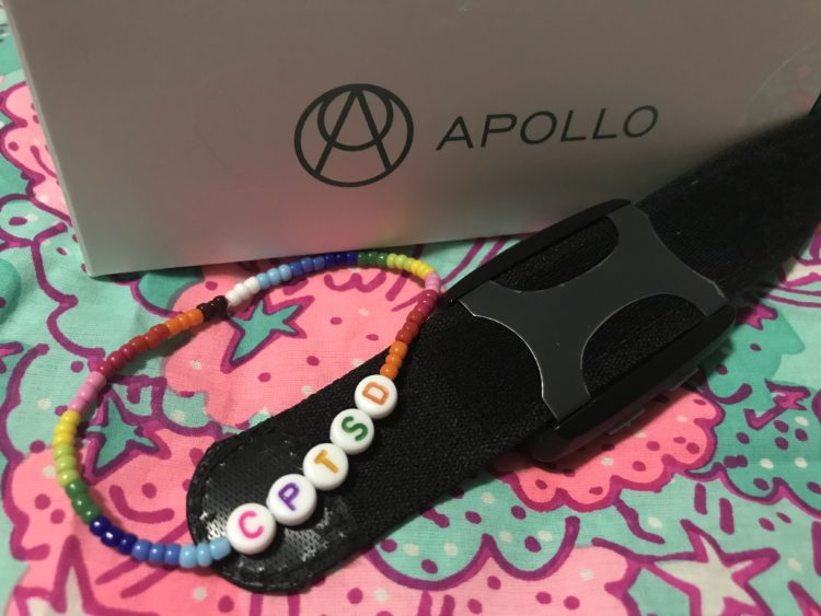 contributor photo showing the Apollo Neuro smartwatch and a braceled saying CPTSD