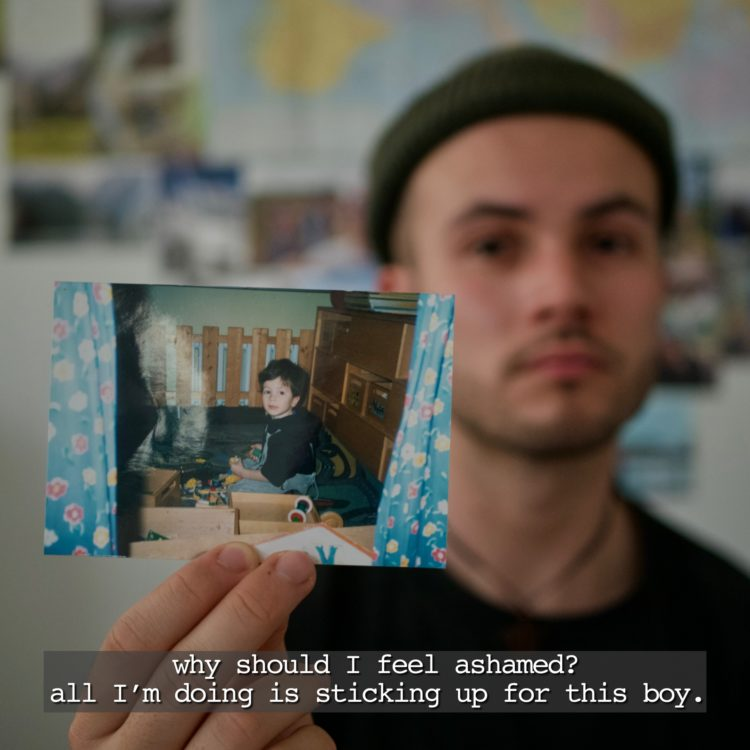 Author: a young, white man wearing a beanie, holding a picture of himself as a child