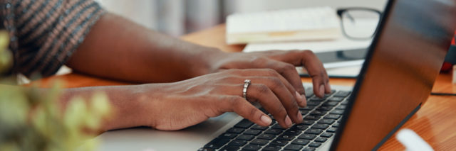 Black woman's hands typing on laptop on desk by pad of paper, glasses and pens