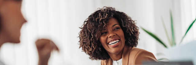 A Black woman laughing in an office meeting